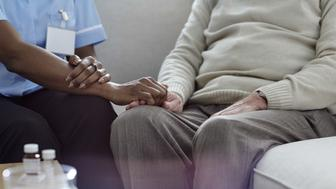Assisted living - Home healthcare nurse consoling elder man. Female nurse holding hand of senior patient.
