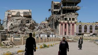 "People walk in front of the remains of the University of Mosul, which was burned and destroyed during a battle with Islamic State militants, in Mosul, Iraq, April 10, 2017. Marko Djurica: ""On April 10, a Reuters team entered eastern Mosul to work on a story about the the city's destroyed university, once a centre for education in northern Iraq. On arrival, I was struck first by the huge size of the campus, then by the scale of destruction. At least 10 large buildings and some smaller ones had been more or less reduced to rubble. The entrance was guarded by Iraqi soldiers, cleaning their guns and drinking tea. I saw people trying to carry furniture and equipment out from what was once the chemistry department in a burnt-out building. It turned out these men were professors who had taught there and had now volunteered to save whatever could be salvaged. As I walked around taking pictures I met more teachers trying to clean up or just gloomily contemplating the devastation. It was emotional for them as they knew there was no chance the university would be the same again anytime soon."" REUTERS/Marko Djurica/File photo   SEARCH ""MOSUL PICTURES"" FOR THIS STORY. SEARCH ""WIDER IMAGE"" FOR ALL STORIES"