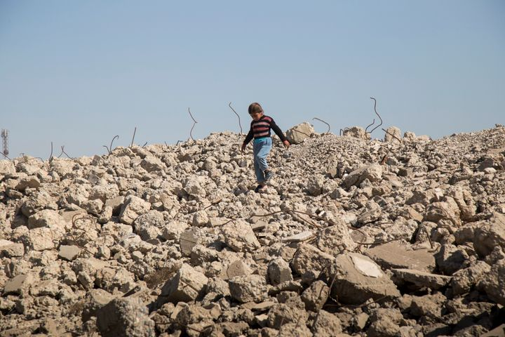 A girl walks amongst the remains of destroyed buildings outside in Hammam al-Alil, a town roughly 25 kilometers south of Mosu