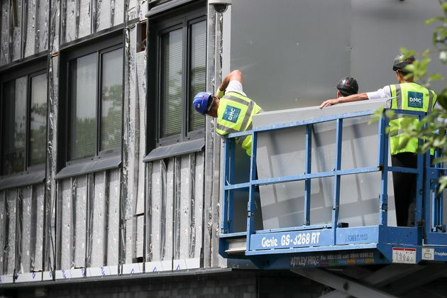 <strong>Workers remove cladding for testing from one of the tower blocks in