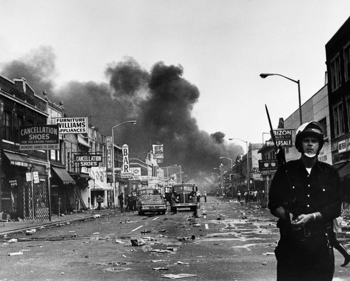 A policeman stands guard in a Detroit street on July 25, 1967, as buildings are burning during riots that erupted following a