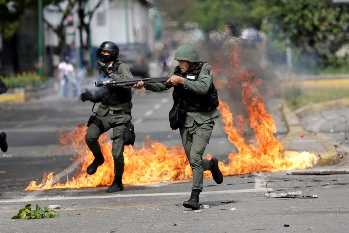 A riot security force member aims his weapon at a rally during a strike called to protest against Venezuelan President Nicola