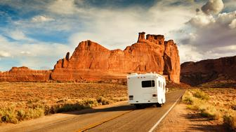 Motor home Camper on a vacation road trip, tourists exploring the American Southwest, the Arches National Park in Utah, USA. The well equipped motor home, traveling a famous scenic highway. Dramatic sky clouds and unique rock formations define the landscape of a popular western recreational travel destination.