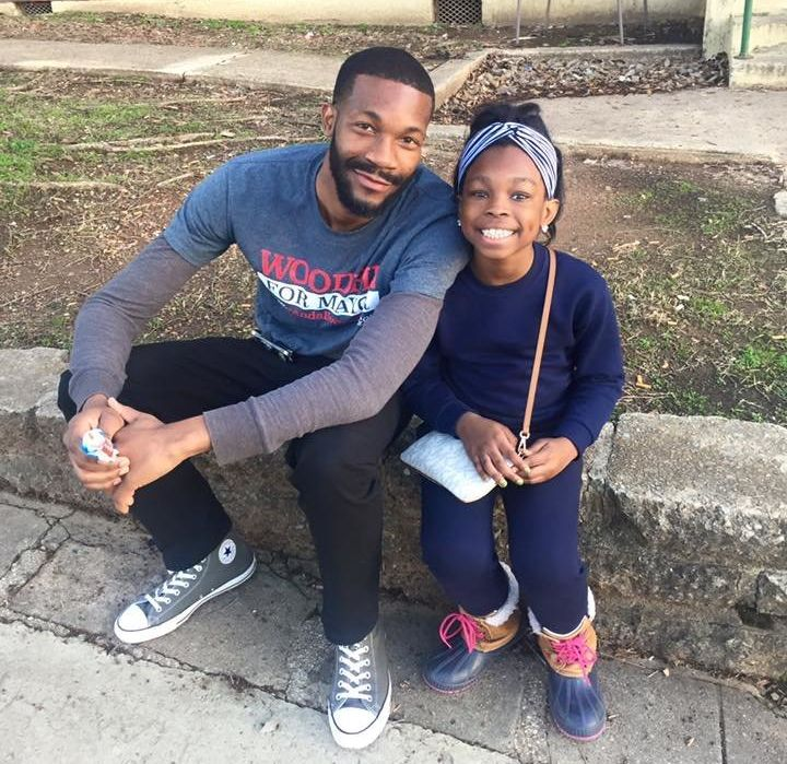 Woodfin shares a moment with a young girl while campaigning in Birmingham's Southtown neighborhood.