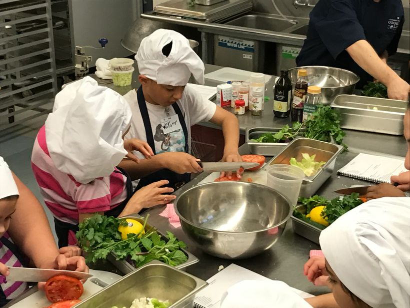 <em>Children sharpen their knife skills while preparing a refreshing salad during a Common Threads Cooking Skills & World