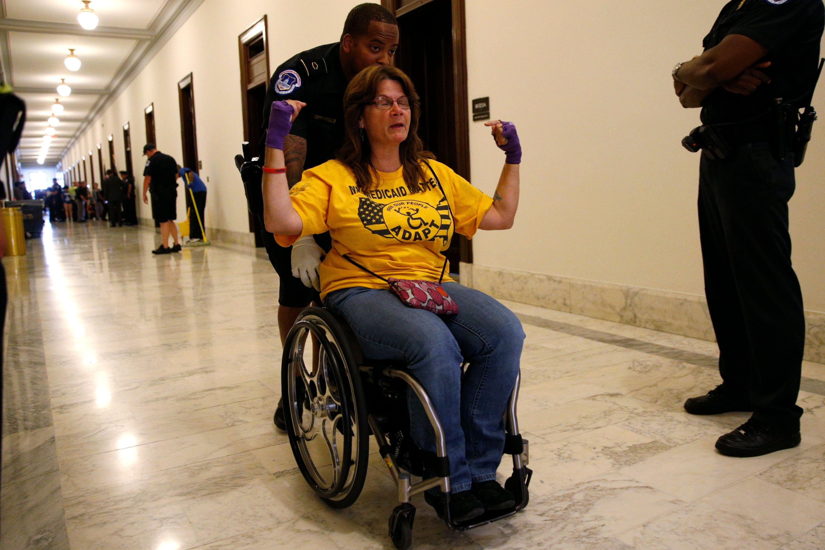 "A protester calling for ""no cuts to Medicaid"" is escorted away by police after being arrested during a demonstration outside Senate Majority Leader Mitch McConnell's office."