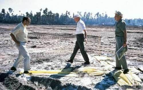 """(L – R) Marty Sklar, Welton Becket, and Dick Irvine stand on a giant yellow """"X"""" in late 1968 which marks the spot where Cinde"""