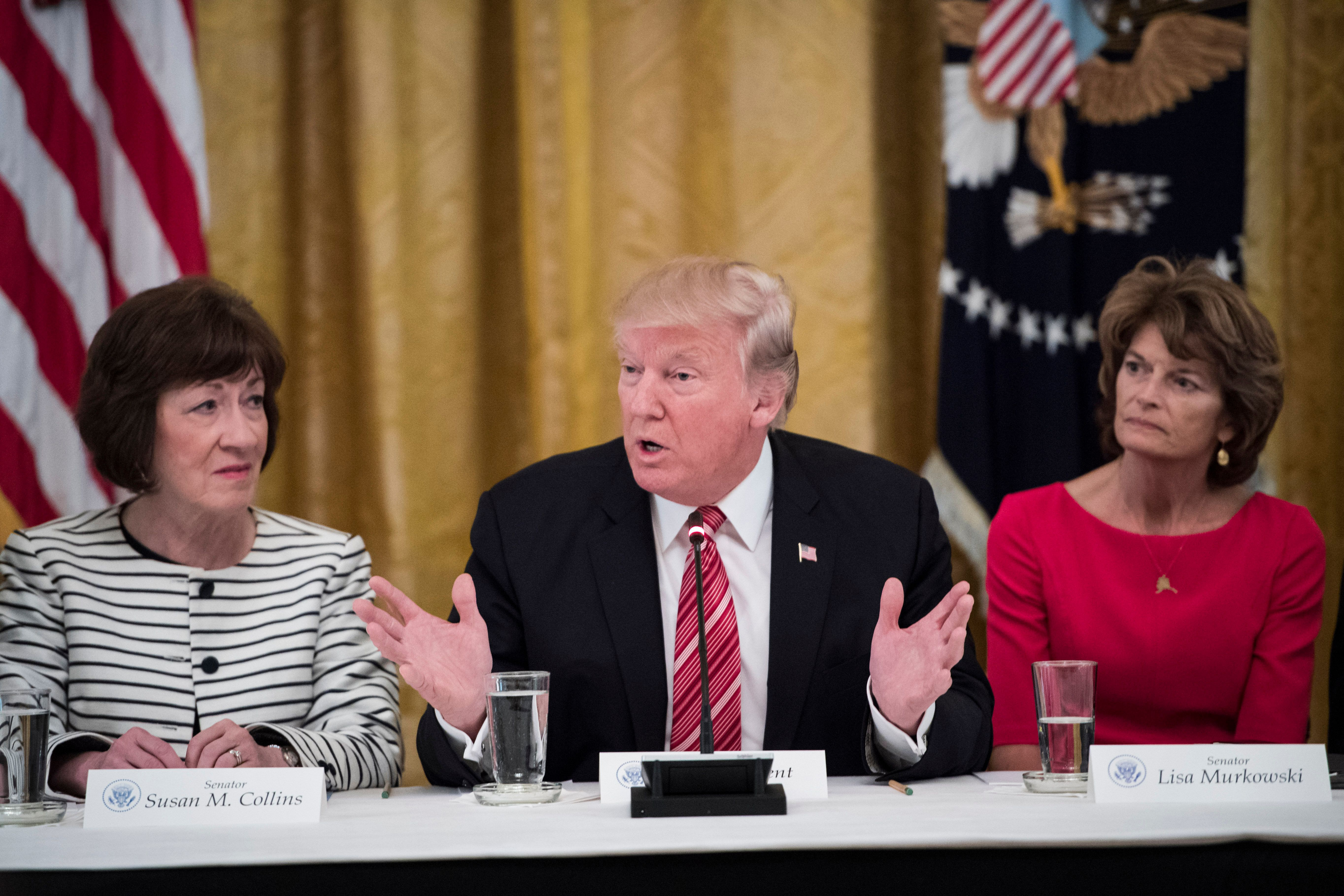 WASHINGTON, DC - JUNE 27: President Donald Trump, center, speaks as he meets with Republican senators about health care in the East Room of the White House of the White House in Washington, DC on Tuesday, June 27, 2017. Seated with him are Sen. Susan Collins, R-Maine, left, and Sen. Lisa Murkowski, R-Alaska, right, (Photo by Jabin Botsford/The Washington Post via Getty Images)