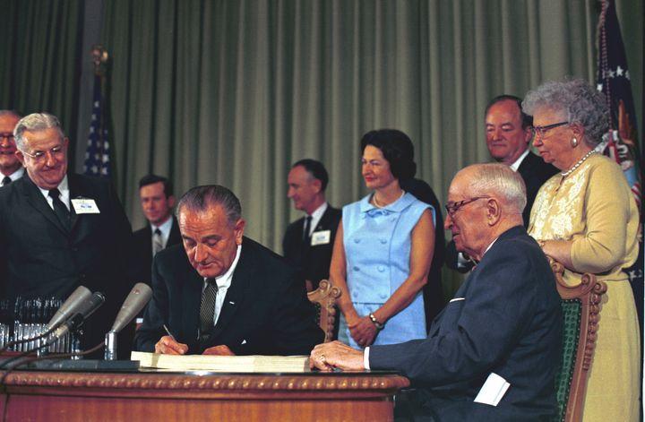 President Lyndon B. Johnson signs Medicare and Medicaid into law.