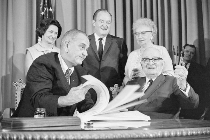 President Lyndon Johnson flips through the pages of the Medicare bill for former President Harry Truman in Independence, Miss