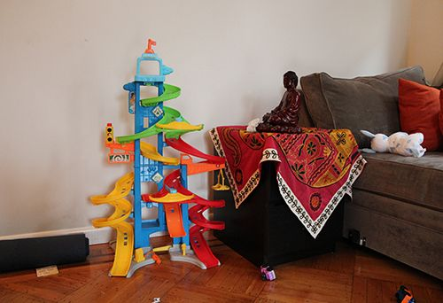 <strong>In the living room: Buddha, yoga mat and child's toys.</strong>
