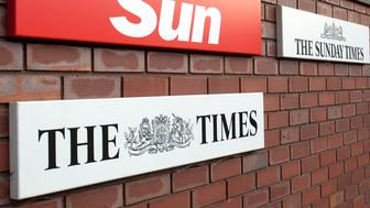 The logos of The Sun, The Times and The Sunday Times newspapers, published by News Corp.'s U.K. News International division, are seen outside the company's headquarters at Wapping in London, U.K., on Thursday, Oct. 20, 2011. Tom Watson, the U.K. lawmaker who has led attacks on Rupert Murdoch's News Corp. over phone-hacking, said he will make new revelations at the company's annual meeting today in Los Angeles. Photographer: Simon Dawson/Bloomberg via Getty Images