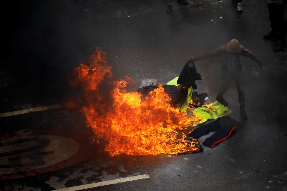 Demonstrators burn police uniforms amid clashes with authorities.