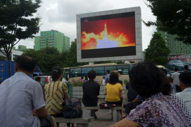 People watch as coverage of an ICBM missile test is displayed on a screen in Pyongyang