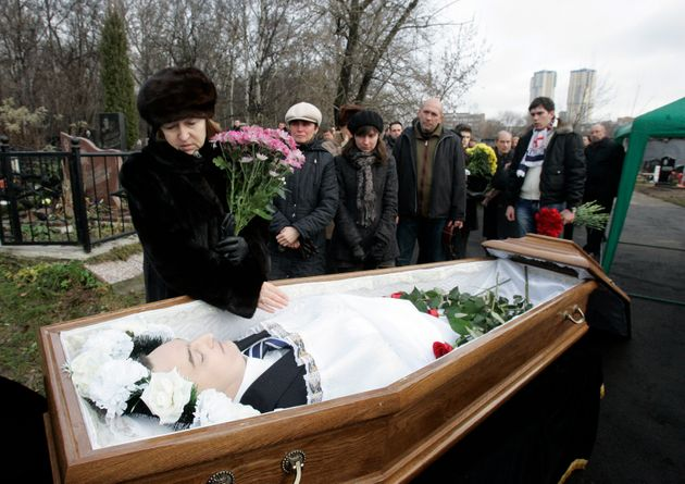 Nataliya Magnitskaya (L), mother of Sergei Magnitsky, grieves over her son 's body during his funeral...