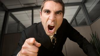A businessman yells and points accusingly at the viewer in a modern office setting.Click on an