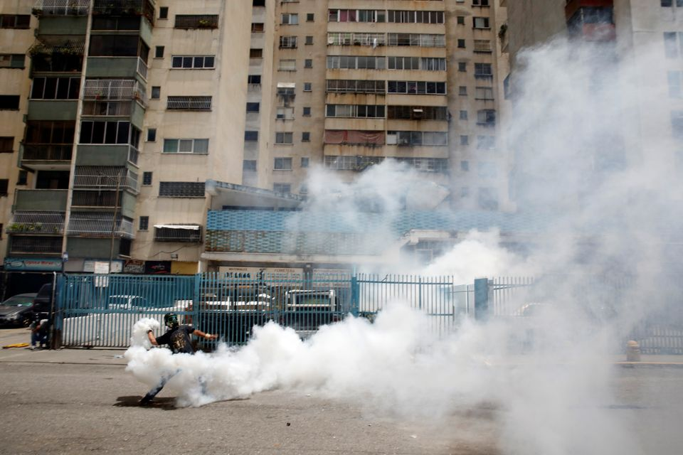 A demonstrator throws back a tear gas canister while clashing with security forces on July 20 in Caracas,