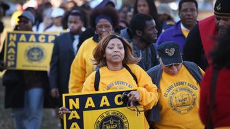FERGUSON, MO - NOVEMBER 29:  Members of the NAACP and their supporters arrive at the Michael Brown memorial to start a  Journey for Justice, seven-day 120-mile march from the memorial to the Governor's mansion in Jefferson City, Missouri on November 29, 2014 in Ferguson, Missouri. The Ferguson area has been struggling to return to normal since the August 9 shooting of Brown, an 18-year-old black man, who was killed by Darren Wilson, a white Ferguson police officer. When the grand jury announced on November 24, that Wilson would not face charges in the shooting rioting and looting broke out throughout the area leaving several businesses burned to the ground.  (Photo by Scott Olson/Getty Images)