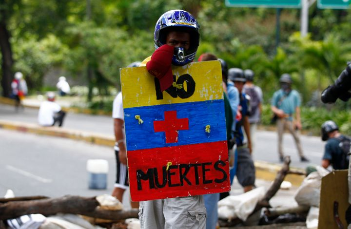 "An opposition supporter holds a shield that reads ""No more deaths"" as clashes break out during Sunday's elections. Caracas. J"