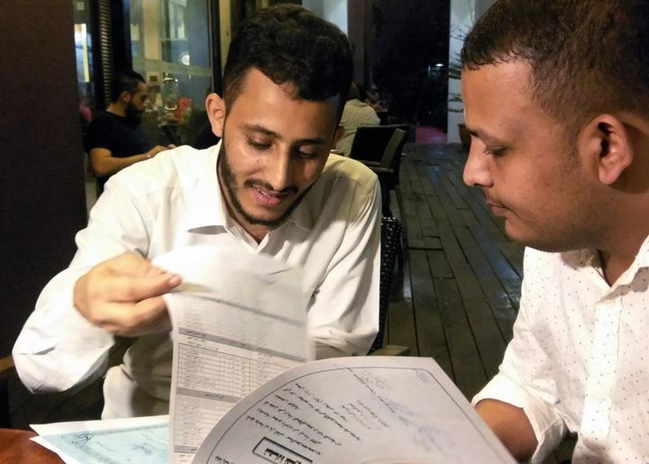 Yemeni Rafek Ahmed Mohammed Al-Sanani (R), 22, and Abdel Rahman Zaid, 26 look through documents as they speak with Reuters in
