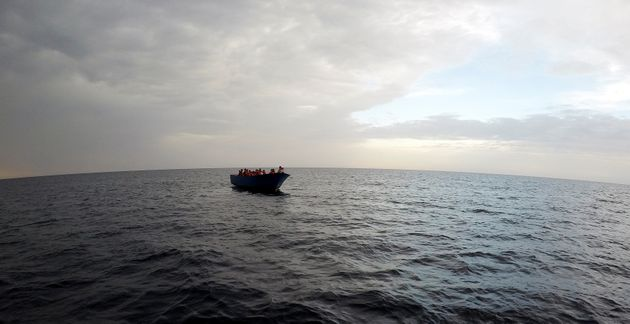 Migrants on a wooden boat wait to be rescued by