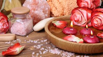 Spa concept with roses, pink salt and candles that float in a wooden bowl with water