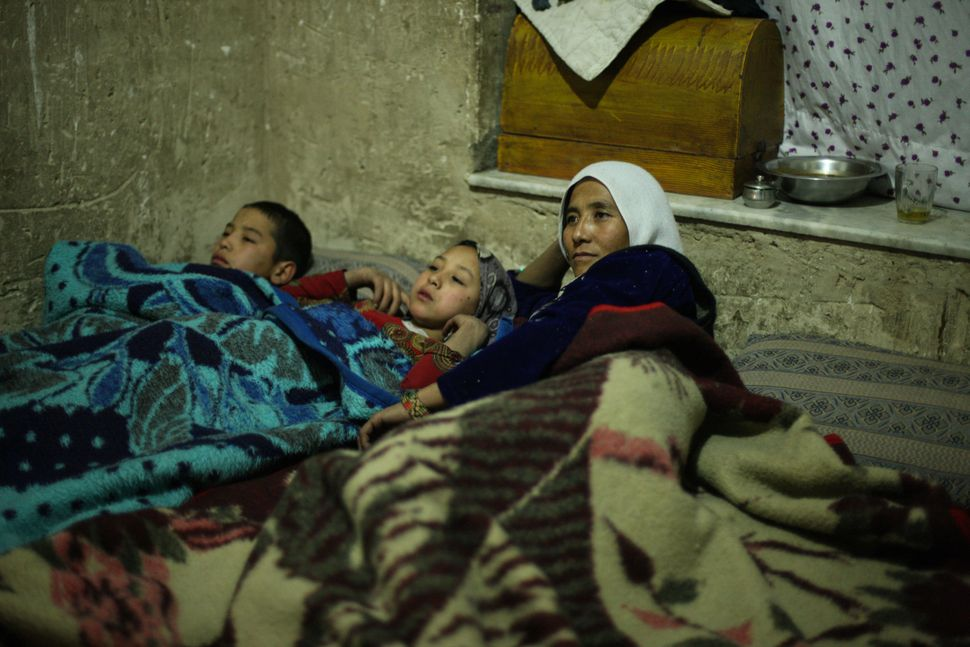 Zakia and two of her children watch TV at the end of the day.