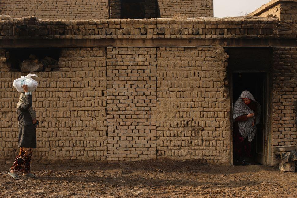 Zakia takes bread to a customer in Kabul.