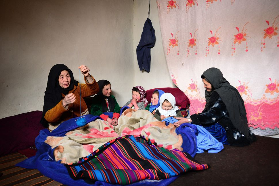 After sowing and cultivation stops, Hamida, 45, right, here with her mother-in-law and children, sews and creates handcr