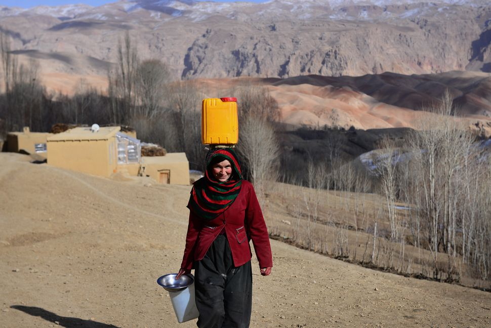 Several times a day, Masooma, 27, carries water on her head from a source more than half a mile from her home.