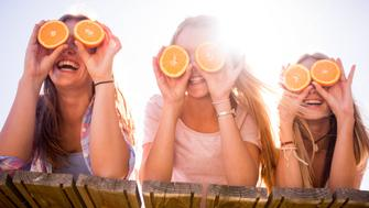 Laughing teen girl friends lying on a wooden jetty holding up oranges over their faces for eyes