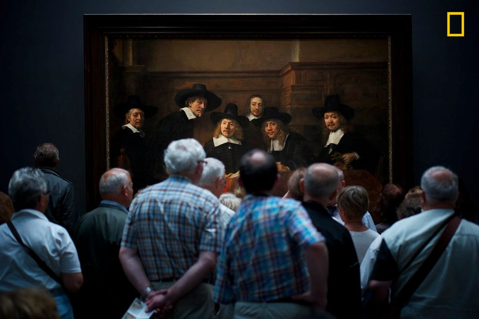 """Museum visitors curiously watch Rembrandt's painting 'Syndics of the Drapers' Guild' [which gives] the illusion that th"