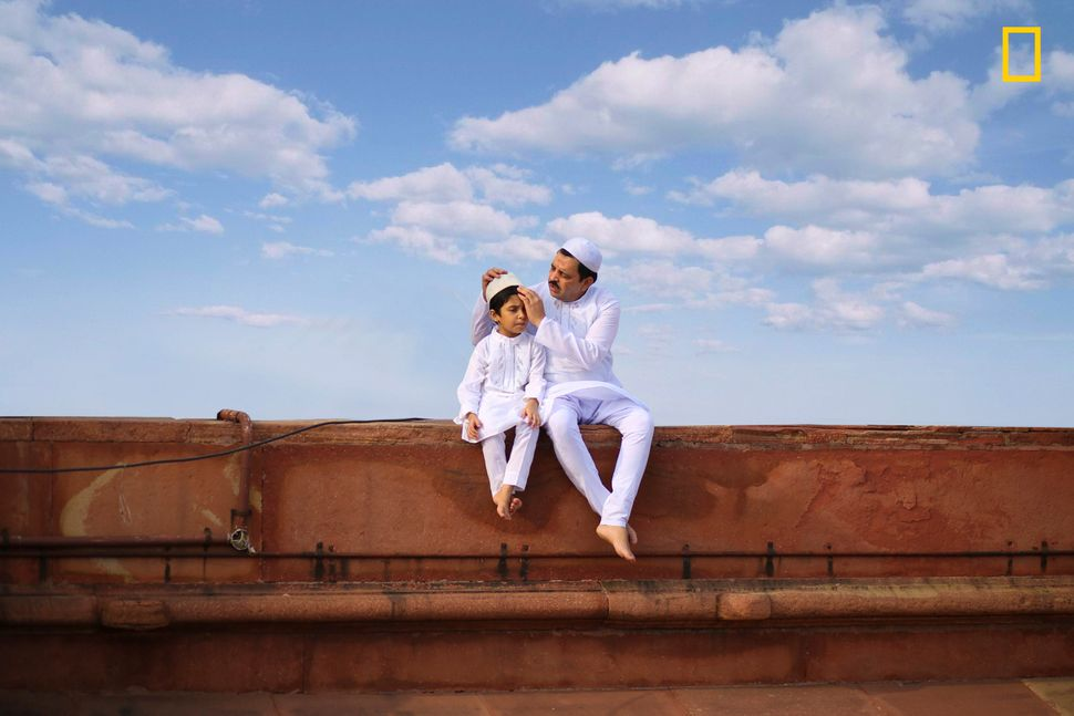 """""""A beautiful photo of a father and son sitting in white traditional attire with beautiful blue sky on the day of Eid al-Fitr"""
