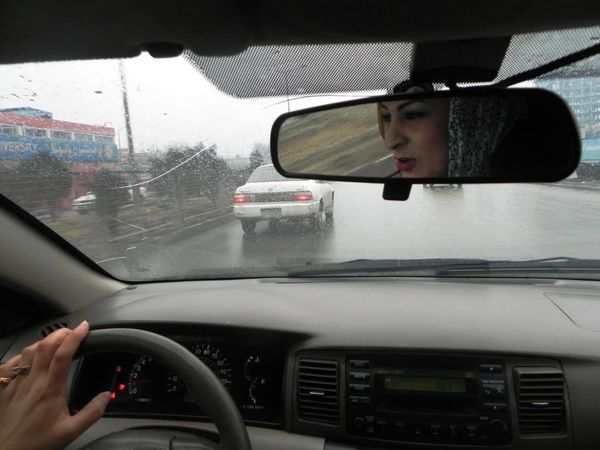 Farahnaz, a young Afghan woman, behind the wheel with an instructor from the Haidari Driving Institute in Kabul.