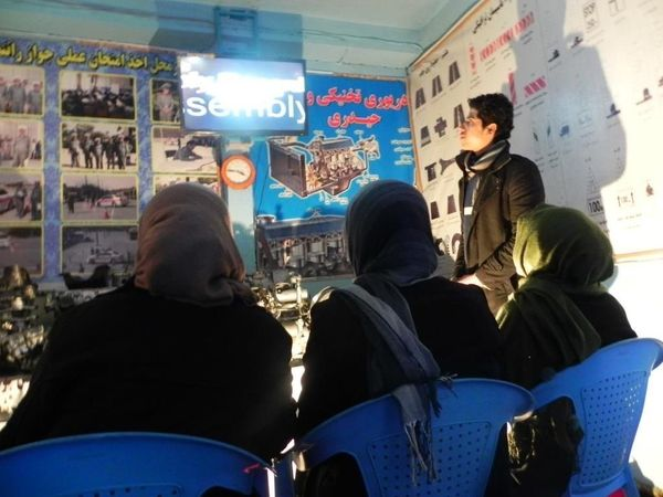 Three womenwatch a safety video at the Haidari Driving Institutein Kabul.