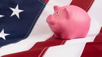 pink piggy bank for  money standing on a US flag