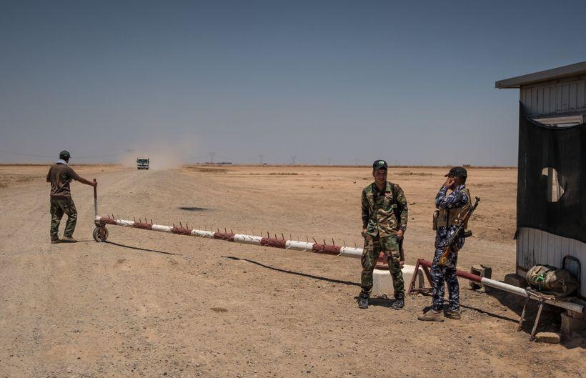 <em>Shiite militiamen guarding the entrance to a desert road in Diyala Province that begins near the Iranian border.</em>