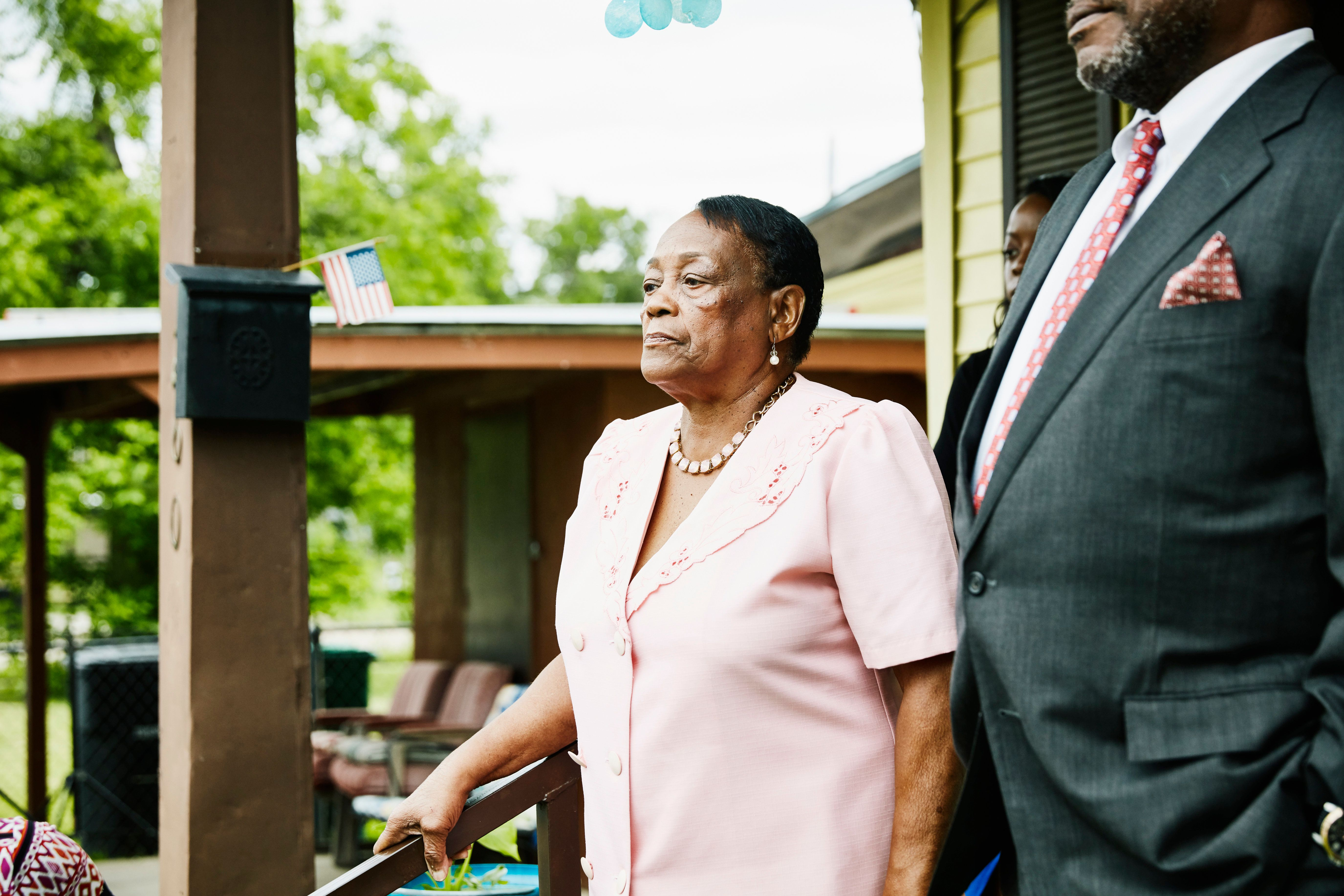 An elderly black woman stands in front of porch dressed ready for church.