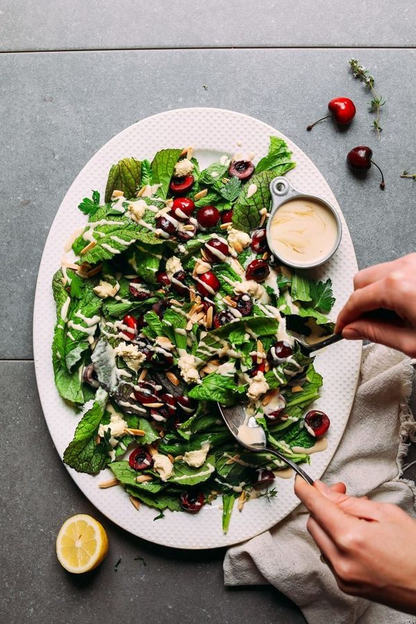 "<strong>Get the <a href=""https://minimalistbaker.com/mustard-green-cherry-salad-with-nut-cheese-tahini-dressing/"" target=""_bl"