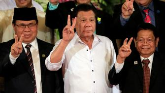 "Philippine President Rodrigo Duterte (C) with Moro Islamic Liberation Front (MILF) chairperson Al Haj Murad Ebrahim (L) and Ghazali Jaafar, MILF vice-chairman flash a ""V"" sign during a handover of a draft law of the Bangsamoro Basic Law (BBL) in a ceremony at the Malacanang presidential palace in metro Manila, Philippines July 17, 2017. REUTERS/Romeo Ranoco"