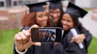 Shot of three female graduates taking a picture of themselves on a phone