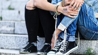Two young girls holding hands, embracing and sitting on stairs. One with rainbow flag on hand. Both with casual clothes. Focus on foreground.