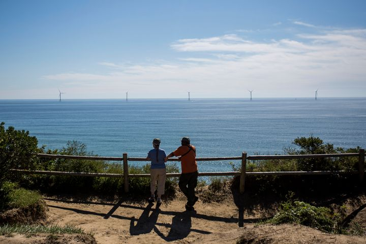 Tourists look out over the Block Island Wind Farm, located 3 miles off New Shoreham, Rhode Island.