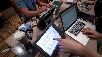 Hackers try to access and alter data from an electronic poll books in a Voting Machine Hacking Village during the Def Con hacker convention in Las Vegas, Nevada, U.S. on July 29, 2017. REUTERS/Steve Marcus