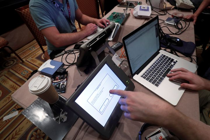 Hackers try to access and alter data from an electronic poll books in a Voting Machine Hacking Village during the Def Con hac