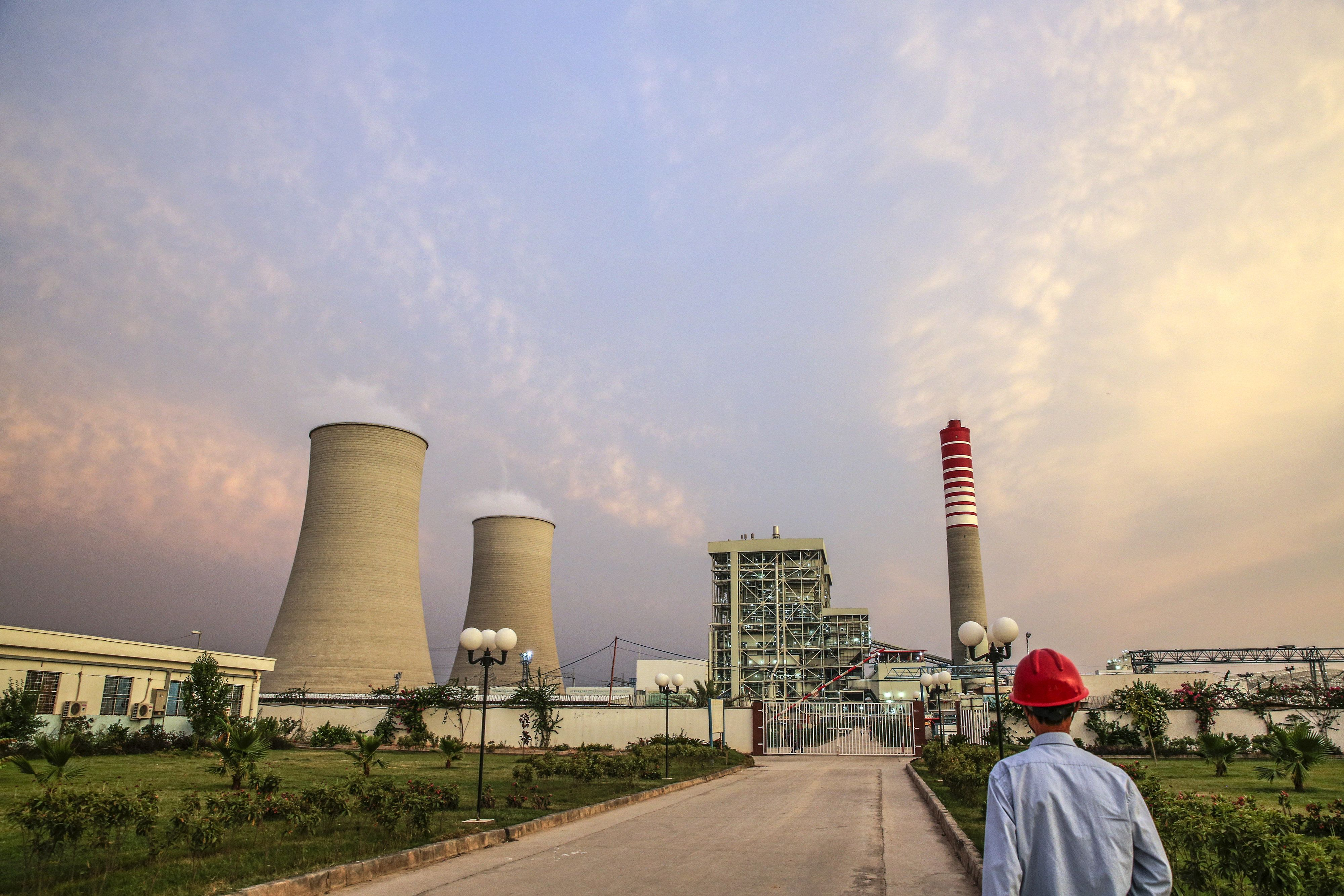 A Chinese worker walks along a path at the Sahiwal coal power plant, owned by China's state-owned Huaneng Shandong Rui Group,