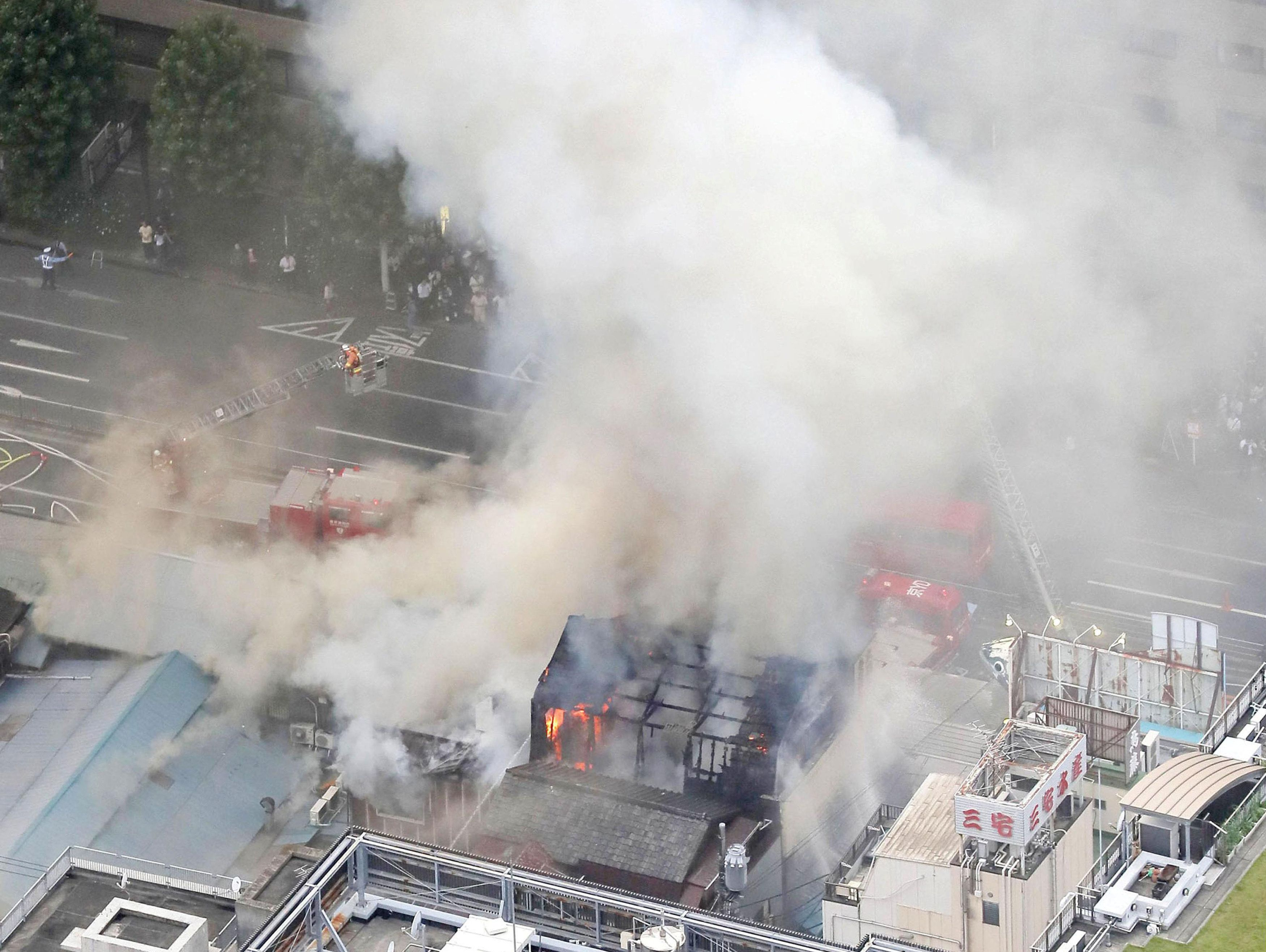 An aerial view shows smoke spews from the fire site at Tsukiji fish market in Tokyo, Japan, in this photo taken by Kyodo August 3, 2017. Mandatory credit Kyodo/via REUTERS ATTENTION EDITORS - THIS IMAGE WAS PROVIDED BY A THIRD PARTY. MANDATORY CREDIT. JAPAN OUT. THIS PICTURE WAS PROCESSED BY REUTERS TO ENHANCE QUALITY. AN UNPROCESSED VERSION HAS BEEN PROVIDED SEPARATELY.