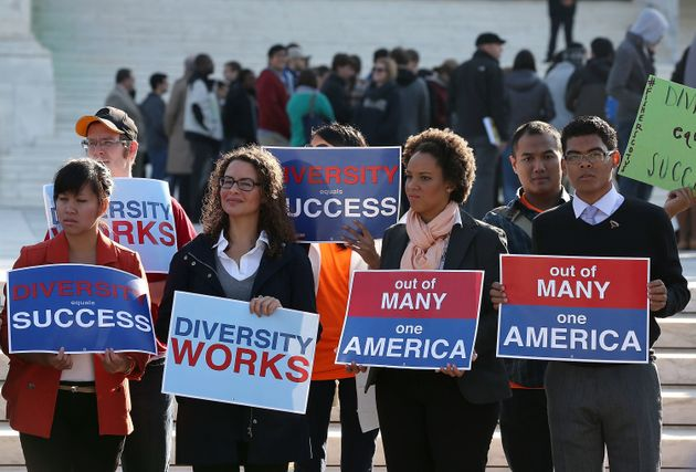 Protesters hold signs in front of the U.S. Supreme Court prior to the high court'sarguments on...