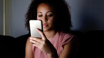 Young girl using her mobile at night on the couch