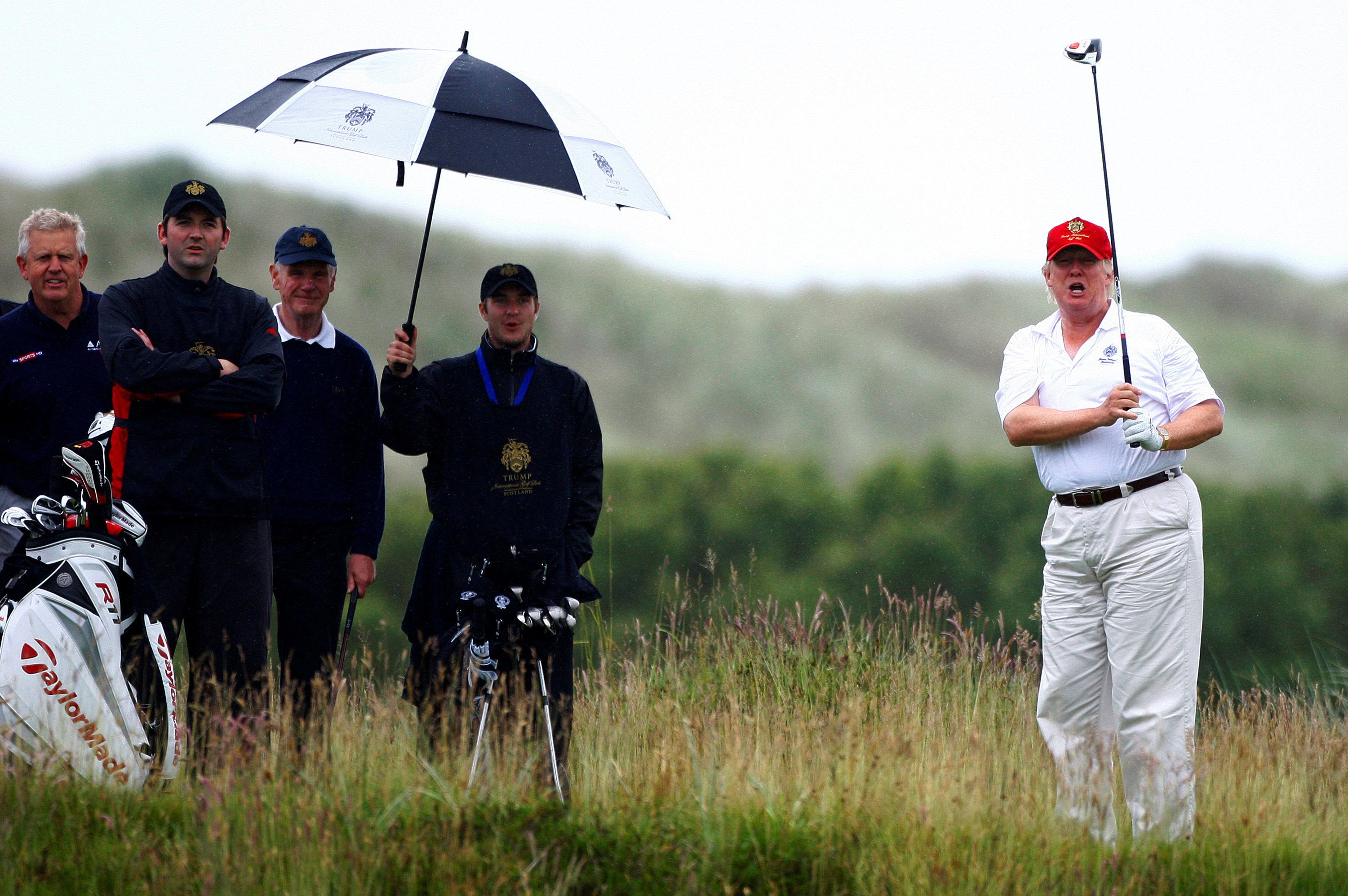 """Real estate magnate Donald Trump (R) plays golf during the opening of his Trump International Golf Links golf course near Aberdeen, northeast Scotland July 10, 2012. REUTERS/David Moir/File Photo                  FROM THE FILES PACKAGE """"THE CANDIDATES"""" - SEARCH CANDIDATES FILES FOR ALL 90 IMAGES"""